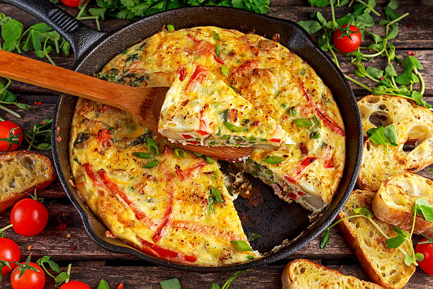 frittata made of eggs, potato, bacon, paprika, parsley, green peas - tortilla stock photos and pictures