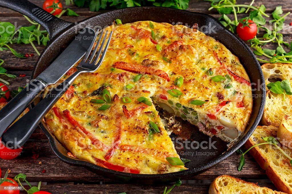 Frittata made of eggs, potato, bacon, paprika, parsley, green peas Frittata made of eggs, potato, bacon, paprika, parsley, green peas, onion, cheese in iron pan on wooden table Appetizer Stock Photo