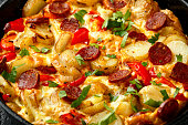 Frittata made of eggs, potato, chorizo, red bell pepper and greens in iron cast pan.