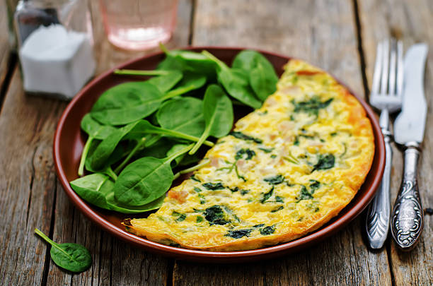 Frittata with chicken and spinach and fresh spinach stock photo