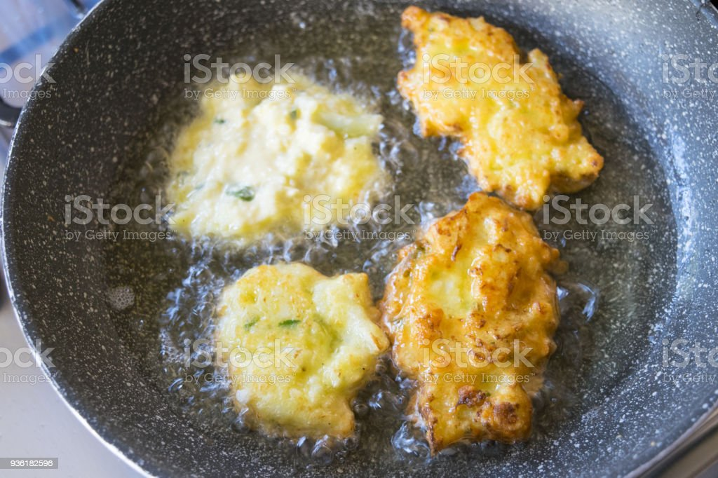 fritters frying in boiling oil stock photo