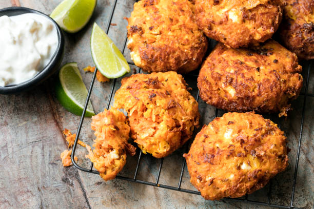 Fritters with Carrot Sweet Potato and Feta Fritters with carrots, sweet potato and feta cheese, served with yogurt and lime. fritter stock pictures, royalty-free photos & images