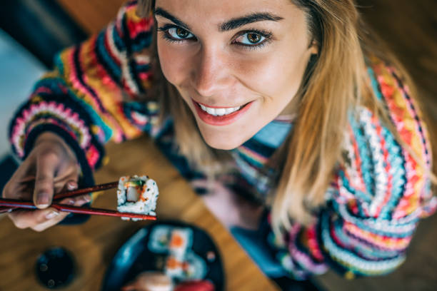 from above Crop woman eating sushi stock photo