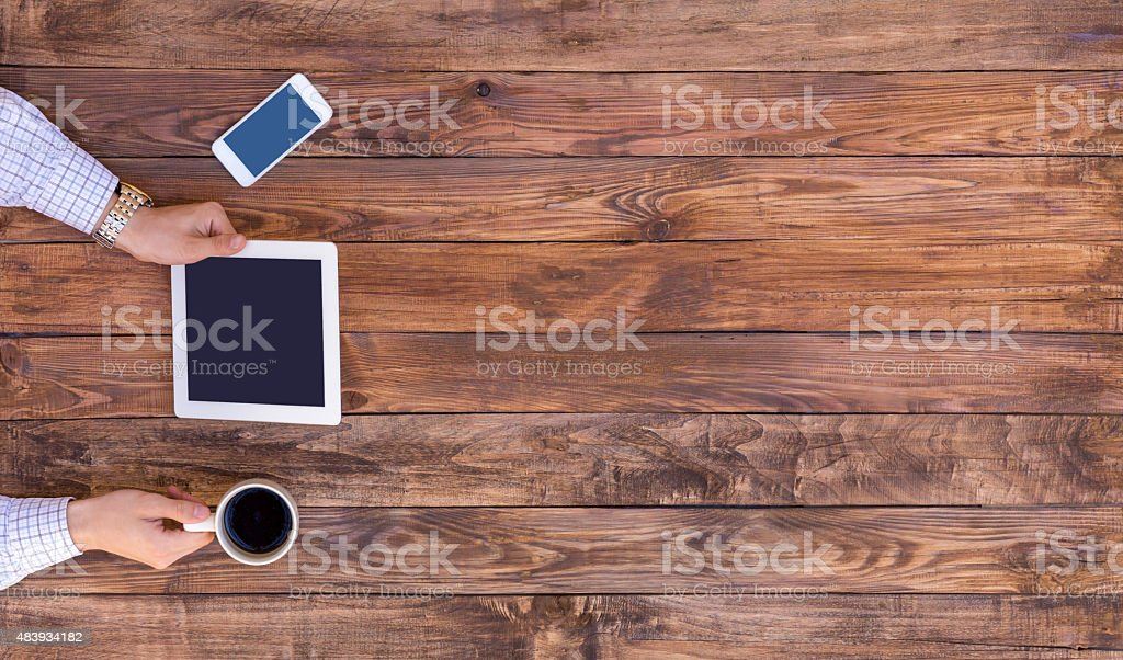 From above image of man browsing gadget empty wood desk stock photo