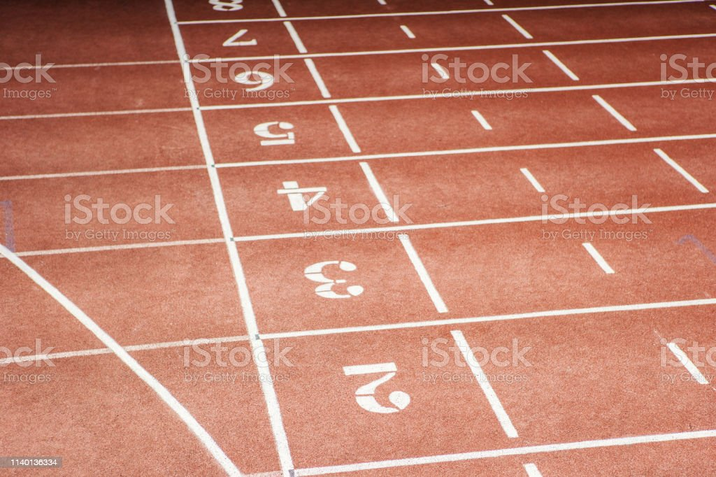 From above view of enumerated running tracks at sports venue with...