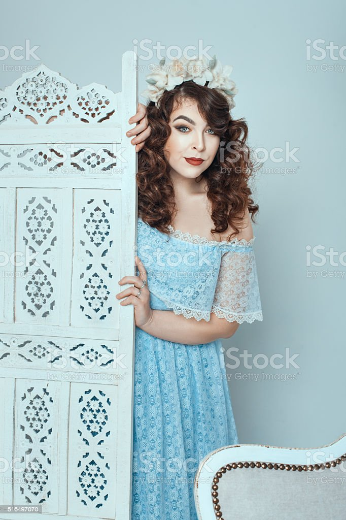 From behind the screen looks a woman. stock photo