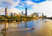 Waters of Brisbane river streaming around Brisbane city CBD high-rise towers in soft morning light with passenger city ferry crossing the river and transporting passangers.