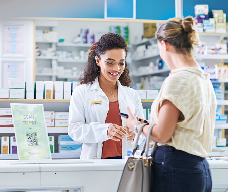 Shot of a young pharmacist assisting a customer in a chemist