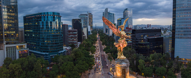 Front aerial view of the statue of the angel of independence on Reforma Avenue with chapultepec forest in the background