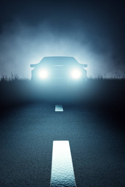 Front Car lights at night on open road Car lights seen from the front on a dark eerie misty night and approaching on a striped asphalt road (3D render) headlight stock pictures, royalty-free photos & images