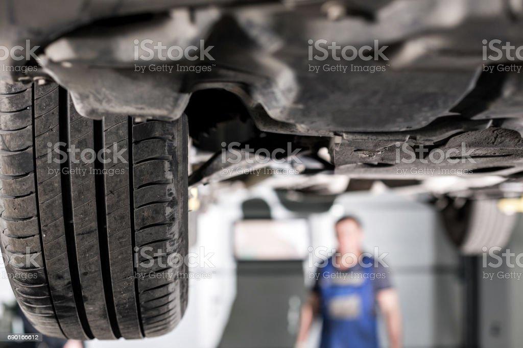 suspensión delantera del coche. el mecánico del garage levantado el coche en el elevador - foto de stock