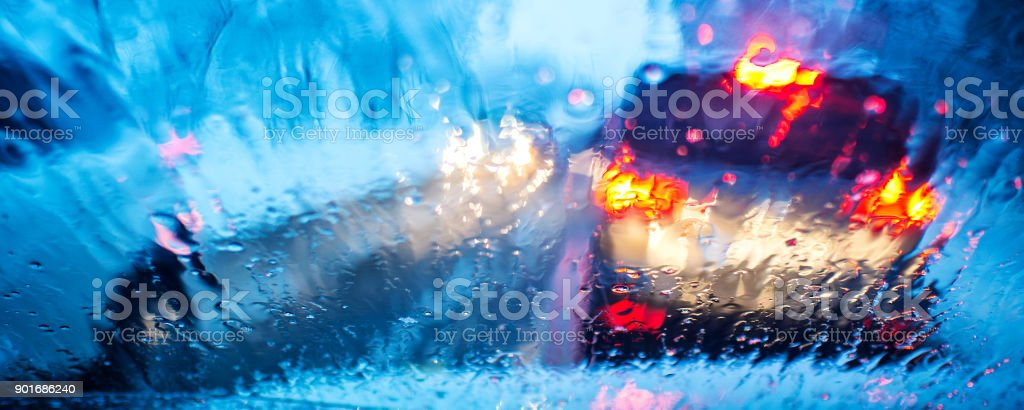 front car window with raindrops and blurred heavy traffic stock photo