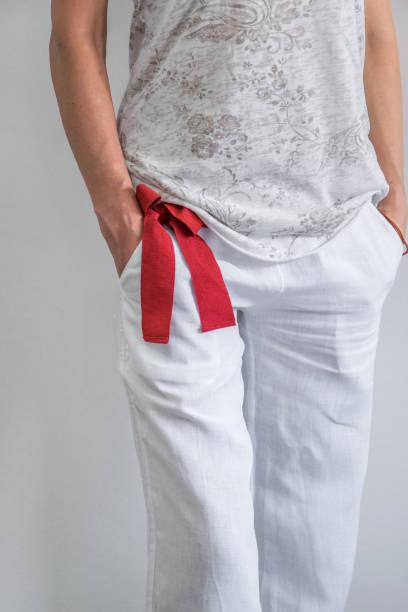 vordere ernte blick auf junge modebewusste frau gekleidet mit weißen leinenhose, t-shirt und ein roter gürtel, gemütliche mode-stil - leinenhosen frauen stock-fotos und bilder