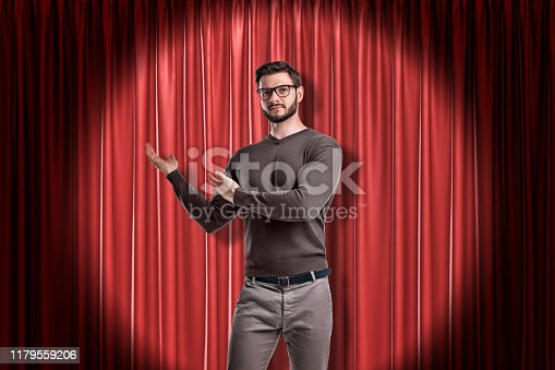 939155332 istock photo Front crop view of young handsome man in casual clothes and glasses standing in spotlight against red stage curtain and making presenting gesture at it. 1179559206