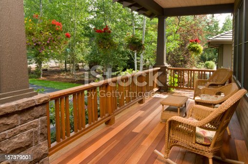 This multi colored hardwood front deck, with wicker chairs gives you a beautiful morning garden view.