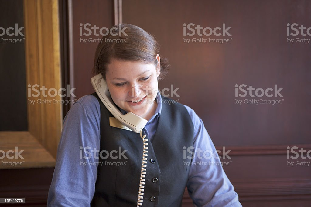 A front desk employer speaking to a guest on the phone royalty-free stock photo