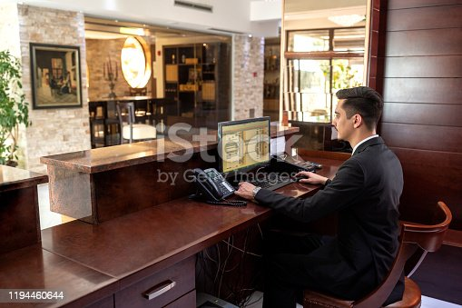 Front desk hotel receptionist working while sitting in the chair