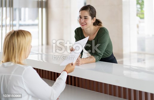 istock Front desk lady offering tourist to fill out documents 1028150968