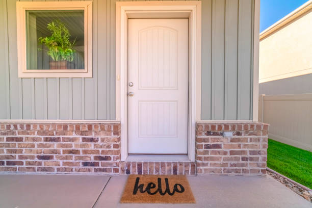 Front door and porch of home with hello mat stock photo