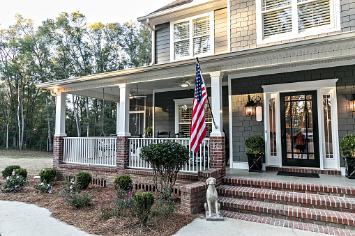 Close up of the front door entrance to a large two story blue gray house with wood and vinyl siding and a large American flag.