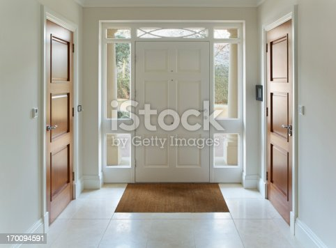 a front door entrance to a grand house. The wood panelled front door and frame are painted white whilst either side, also in white frames are two wooden doors for two separate cloakrooms. Inset into the cream coloured marble floor is bristle floor mat. Through the glass that surrouds the front door frame one can see part of a carriage drive whilst two columns sit either side on the outside of the front door.