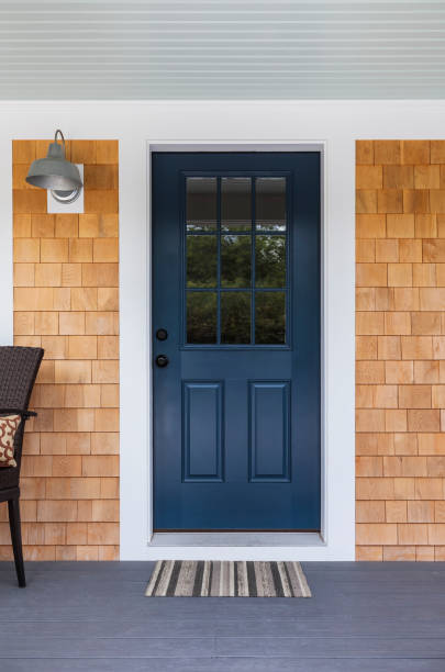 front door, exterior view Front dark blue door with white accents and wood siding with a nice porch light and a comfortable chair and a welcoming doormat front door stock pictures, royalty-free photos & images