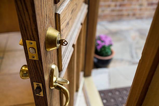 Front Door Left Open with Key in Lock Front Door Left Open with Key in Lock - Home security breach with front door left open with key in lock. front door stock pictures, royalty-free photos & images