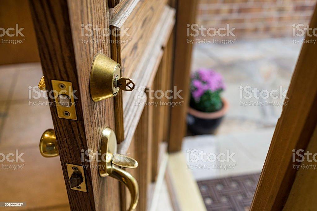 Front Door Left Open with Key in Lock stock photo
