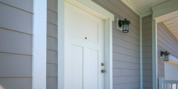 Front door of a home with a lamp on the gray wall stock photo