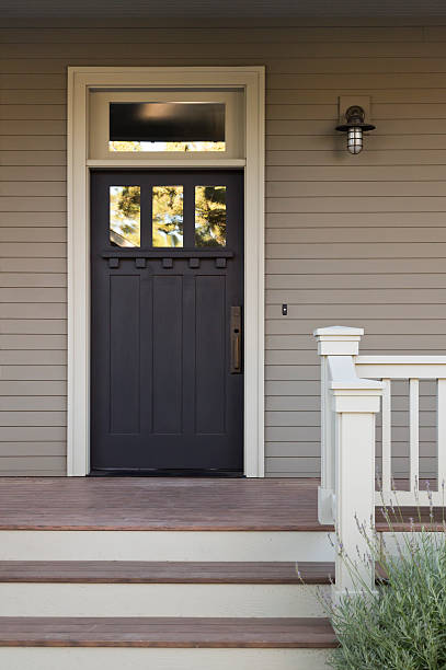 Front Door of an Upscale Home Front view of a black front door with white trim on a gray house, with view of front steps and porch light. Vertical shot.  front door stock pictures, royalty-free photos & images