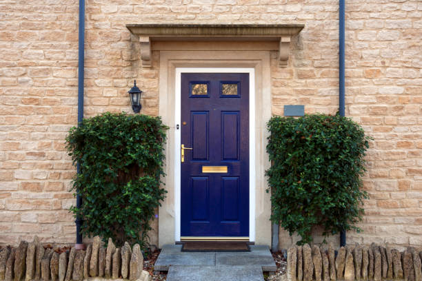 Front door Modern blue painted front door flanked by shrubs front door stock pictures, royalty-free photos & images