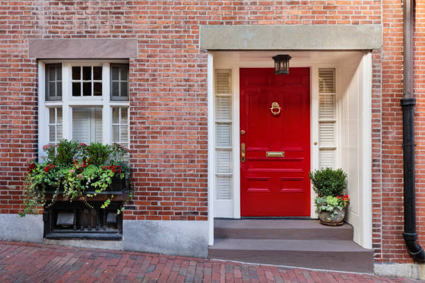 Front door, red front door A front view of a brick house along the sidewalk with an abundance of flowering plants in the windowsill. The door is painted in a deep red color. front door stock pictures, royalty-free photos & images