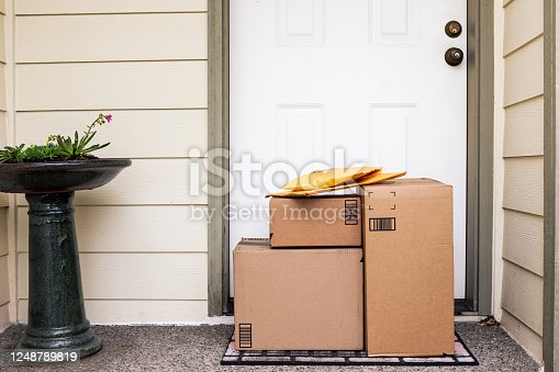 Front Door of House with Stack of Delivery Boxes from Online Ordering and E-commerce