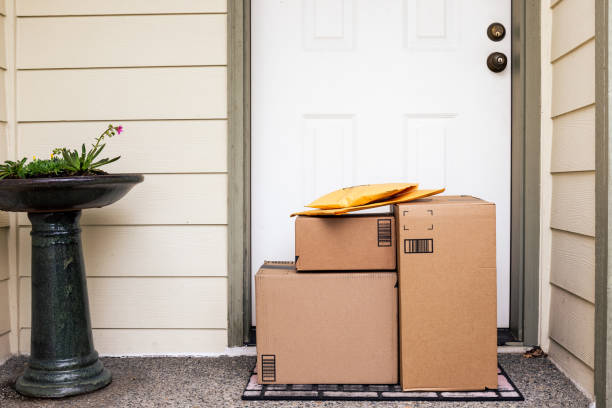 Front Door with Delivery Boxes Front Door of House with Stack of Delivery Boxes from Online Ordering and E-commerce front door stock pictures, royalty-free photos & images