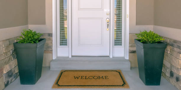 Front door with doormat plants and glass panel Front door with doormat plants and glass panel. White front door of a house with the word welcome printed on the brown doormat. Ornamental plants and glass panels are on each side of the door. front door stock pictures, royalty-free photos & images