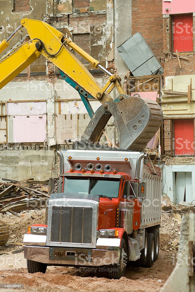 Front End Loader Dropping Demolition Scrap Materials Into Dump Truck royalty-free stock photo