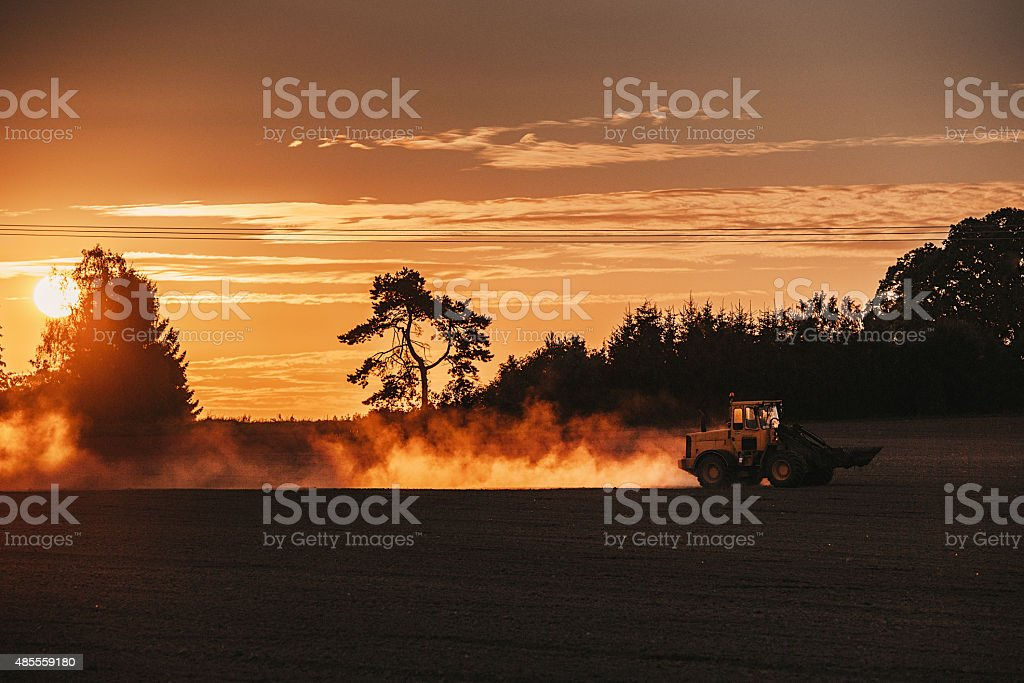 Front end loader on field in sunset stock photo