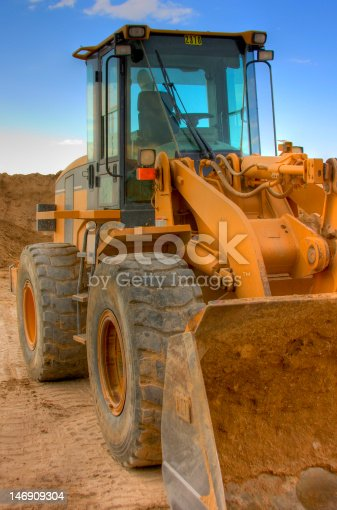 A front end loader on a construction site under a vibrant blue sky. (HDR)