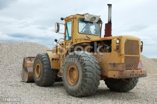 Angled shot of a front end loader at a rock pile.