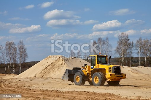 Front end loader scoops up a sand near an aerated concrete plant