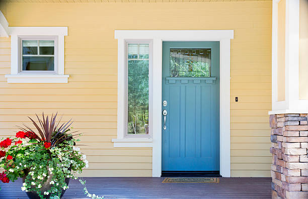 Front entrance of a home with blue door A front entrance of a home with a blue door, yellow siding, and a flowerpot in daytime. front door stock pictures, royalty-free photos & images