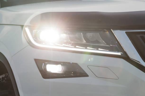 白色汽車的前大燈視圖,打開 LED 日運行 DRL 燈和雙 Xenon 鏡頭圖像檔