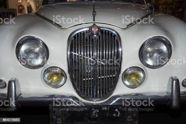 Moscow, Russia - April 02, 2017: Front headlights and grille of a restored white Jaguar S-type, 3,8 litre, Great Britain 1965, close up frontal. Retro car exibition in shopping mall Metropolis.