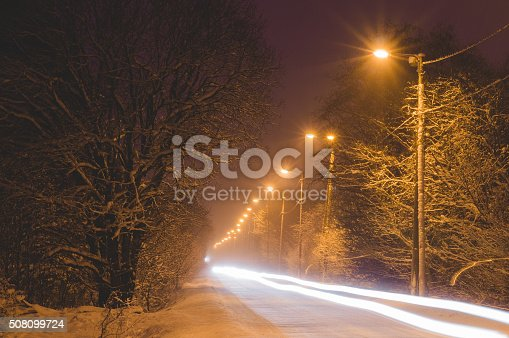 657042754 istock photo Front lights of car on snowy road by winter night 508099724