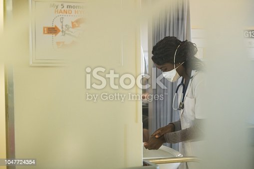 Front line healthcare worker wearing a protective TB mask and washing her hands
