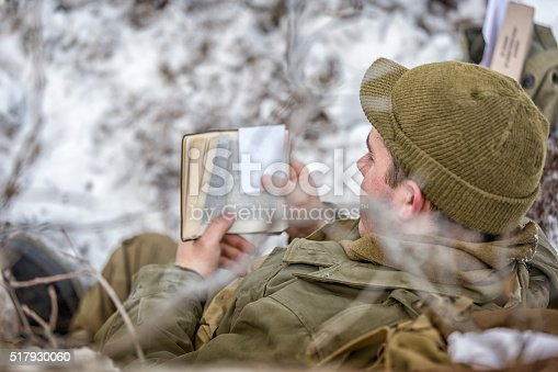 Stock photo of a soldier reading the bible on the frontlines in a fortified postion