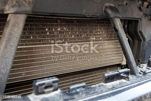istock Front of a repaired car with a view of the grille. Search for coolant leakage antifreeze 1248488345
