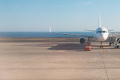 front of airplane standing on runway with ocean background