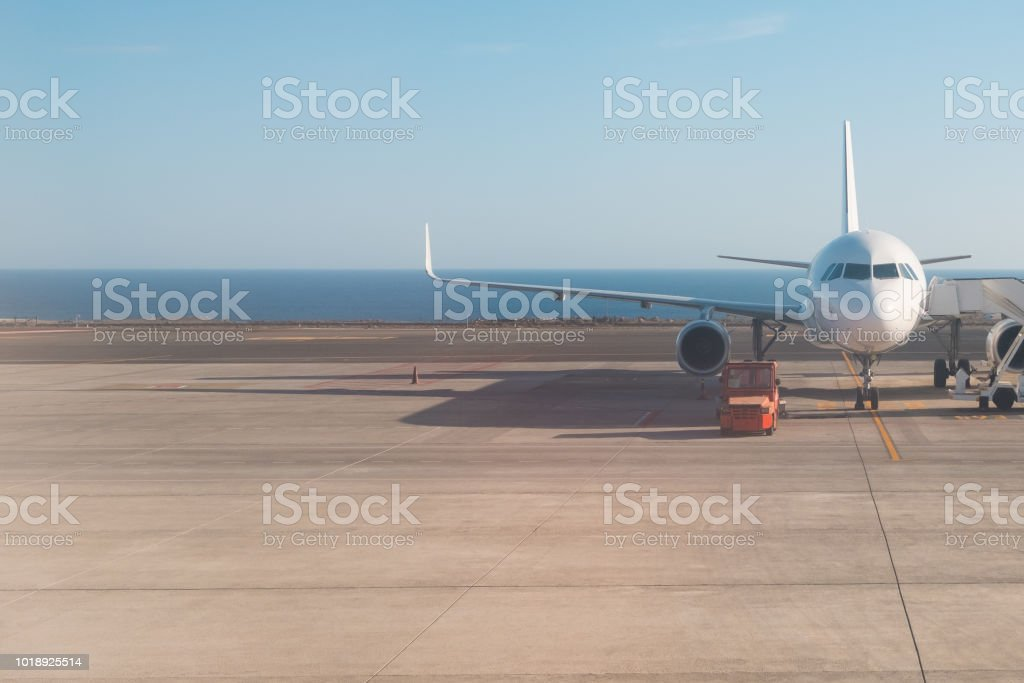 front of airplane standing on runway with ocean background stock photo