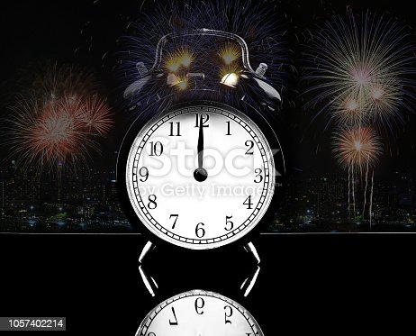 istock Front of alarm clock analog classic vintage style on black table, with Red, Yellow, Blue, Green, Fireworks on midnight background, Holidays Happy New Year concept. 1057402214